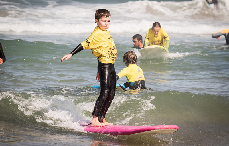 Young boy learns to surf at moana surf school